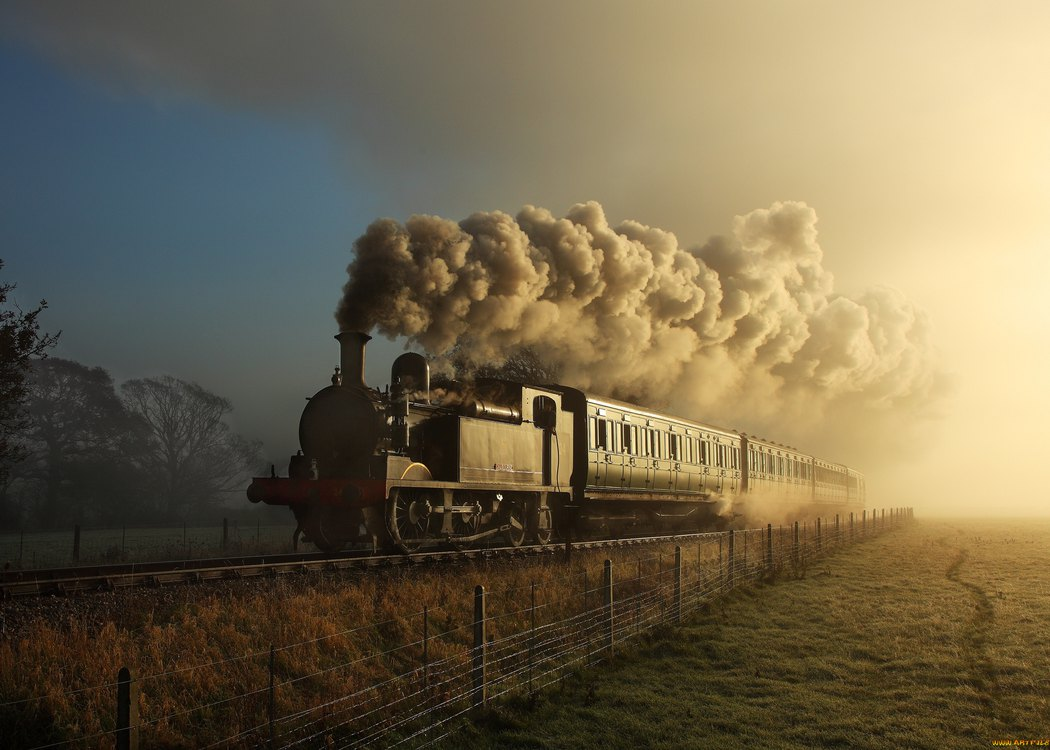 Perspective view on the rails in the countryside; a freight train comes with the dense smog